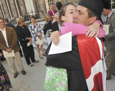 Graduate Craig Gibson, of Winchester, Mass., gets a hug from his daughter Caroline Gibson, 11, after commencement of Master of Arts in Ministry at St. John&#39;s Chapel at St. John&#39;s Seminary, Wednesday, May 20, 2009 in Brighton, Mass. (Photo by Lisa Poole)