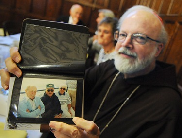 Cardinal Sean O'Malley poses with a gift (albums of photos including this photo of his parents) given to him following a service with the Serrans at the chapel of St. John's Seminary in Brighton, Mass., Friday, June 26, 2009. (Photo/Lisa Poole)