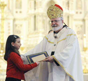 Cardinal Sean O'Malley gives Michelle Beazley the Blessed Mother Teresa of Calcutta award during an altar server appreciation mass at the Cathedral of the Holy Cross, Boston, Saturday, Oct. 31, 2009. (Photo/Lisa Poole)