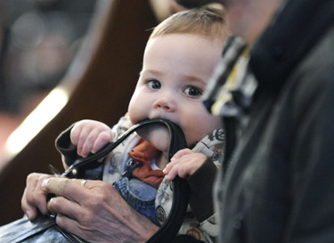 Gerard Sullivan, 8 months, of Boston, chews on a pocketbook strap as he sits with his grandmother Gerry Sparks, of Boston (not shown) during the Litergy of Good Friday with Sen Cardinal OMalley at the Cathedral of the Holy Cross in Boston, Friday, April 2, 2010. (Photo/Lisa Poole)