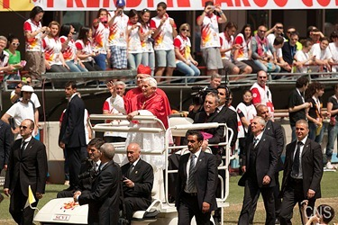Pope Benedict XVI, flanked by Milan Cardinal Angelo Scola, waves as they arrive at San Siro stadium in Milan June 2. The pope was in Milan for the 2012 World Meeting of Families. (CNS photo/Maria Grazia Picciarella, pool) (June 4, 2012) See stories marked FAMILIES- June 1-4, 2012.