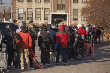 People line up to receive turkeys during the Thanksgiving Project outside Catholic Charities El Centro del Cardenal Food Pantry in Boston&#39;s South End on Saturday, December 17, 2012. The Thanksgiving Project was a collaboration between the United Way of Massacusetts Bay and Merrimack Valley to provide Thanksgiving Meals to 7,000 families this holiday. Catholic Charities distributed over 3,000 of the meals at their sites. (Photo by Suzanne Ouellette/Catholic Charities)