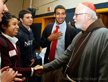 MARY SCHWALM/Staff photo Cardinal Sean P. O'Malley shakes hands with Notre Dame Cristo Rey High School student Natalya Villa as her friends Elie Azzi and Miguel Monclova, second right, look on in they gym at the school after participating in 10th anniversary mass of celebration and thanksgiving at St. Mary's Church in Lawrence.   10/9/13