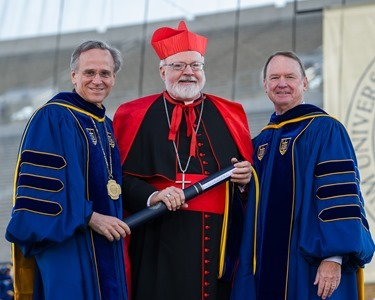 May 18, 2014; University of Notre Dame president Rev. John Jenkins, C.S.C., left, and Notre Dame Board of Trustees chairman Richard Notebaert, right, present an honorary degree to Cardinal Seán Patrick O'Malley, O.F.M. Cap. at the 2014 Commencement ceremony in Notre Dame Stadium.