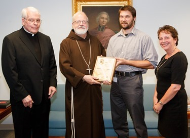 "Pilot staff reporter Christopher S. Pineo receives his plaque of the Pontifical Mission Societies' Archbishop Edward T. O'Meara Award from Cardinal Seán P. O'Malley Aug. 13, 2014. Pineo took first place in the category of Mission Animation News for his Aug. 30, 2013 story ""Plymouth Religious Ed Students Use Lemonade Stand to Spread the Good News."" First presented in 1993, the award recognizes excellence in coverage of world mission news in the Catholic press.<br /> Pilot photo/ Gregory L. Tracy<br />"