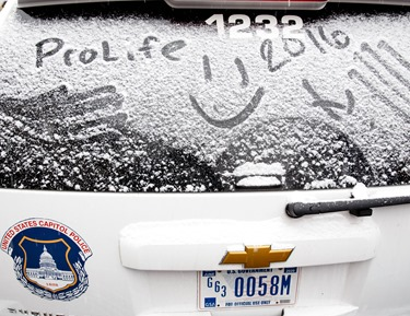 A prolife message is written on the on the snow-covered window of a U.S. Capitol Police patrol car parked front of the U.S. Supreme Court during the 2016 March for Life Jan. 22. Pilot photo/ Gregory L. Tracy