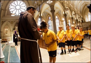 Students from the parish school of Immaculate Conception Parish in Lowell, Mass. venerate the relic of the heart of St. Padre Pio Sept 21, 2016. Their parish was the first stop of a three-day visit of the relic to Boston. Pilot photo/ Gregory L. Tracy