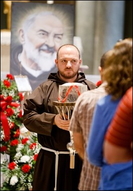 The faithful venerate the relic of the heart of St. Padre Pio at Immaculate Conception Church in Lowell, Mass. Sept 21, 2016. The relic is on a three-day tour of the Archdiocese of Boston, which will culminate with a Mass celebrated by Cardinal Seán P. O'Malley on the saint's feast day, Sept. 23. Pilot photo/ Gregory L. Tracy
