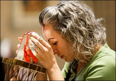 A woman venerates the relic of the heart of St. Padre Pio at Immaculate Conception Church in Lowell, Mass. The church was the first stop in a Sept. 21 – 23 tour of the relic to the Boston area. This trip marks the first time a major relic of St. Padre Pio has travelled outside Italy.Pilot photo/ Gregory L. Tracy